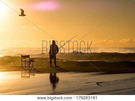 Fishermen with fishing rod at sunrise on beach