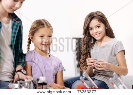 Full of positive emotions. Cute upbeat pretty kids sitting in the robotics laboratory and testing cyber devices while having science lesson
