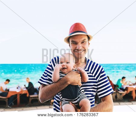 Smiling father with cute baby son having fun on the coast near sea beach. Happy family relaxing by the sea. Coast of Croatia