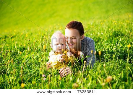 Beautiful mother with baby child son lying on the green grass of meadow in summer day. Family on nature.