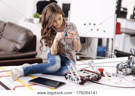 Revealing my talent. Involved clever capable girl sitting in the robotics laboratory and holding details of cyber robot while expressing interest
