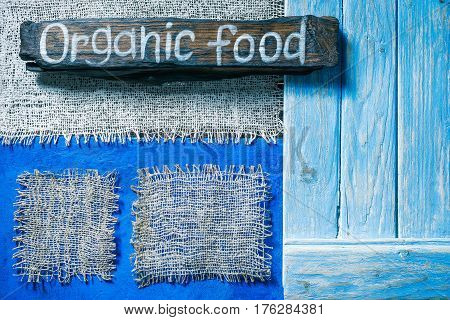 Burlap frames on blue painted wood boards. Dark wooden signboard with text 'Organic food' as title bar. Structured shabby style background for natural food and drink industry