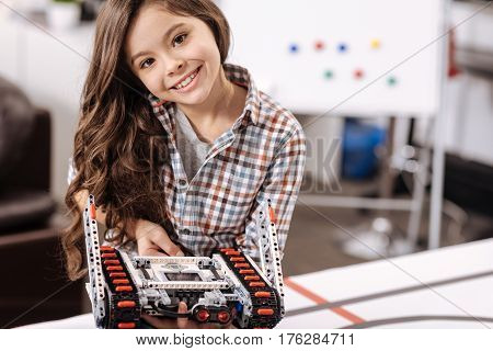 Look at this electronic toy. Charming smiling pleasant girl sitting in the robotics laboratory and holding cyber robot while expressing joy