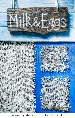 Burlap frames on blue painted wood boards. Dark wooden signboard with text 'Milk an eggs' as title bar. Structured shabby style background for natural food and drink industry