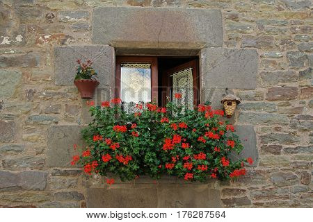 Window with white curtains birdhouse hanging pot and decorated Geranium flowers in Rupit (Catalonia Spain)