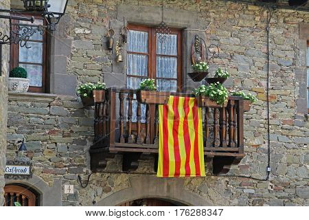 Rupit Spain - September 09 2014: Balcony with white petunias and Catalan flag in Rupit (Catalonia Spain)