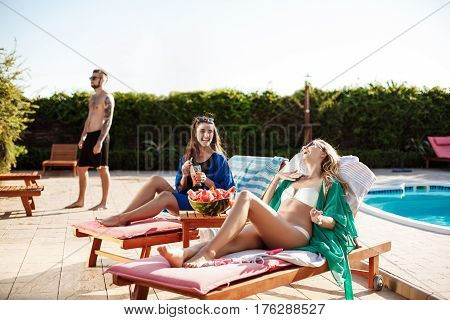 Attractive girls smiling, sunbathing, drinking cocktails, lying on chaises near swimming pool. Copy space.