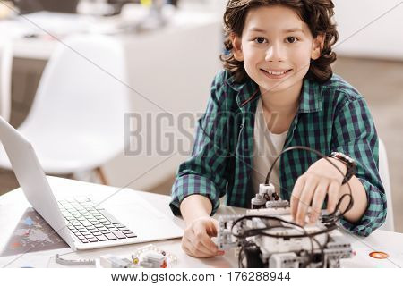 Like a proficient programmer. Smiling gifted capable boy sitting in the studio and working with electronic gadgets while studying and expressing joy