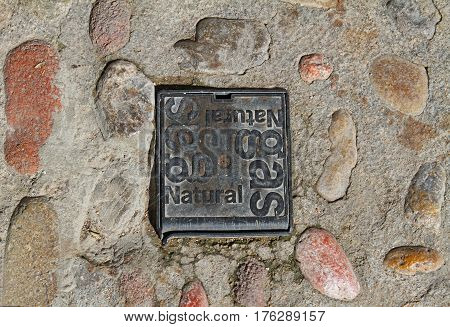 Iron cast hatch of Natural gas on the paving road in Besalu (Catalonia Spain)