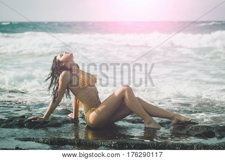 Pretty Girl In Sexy Yellow Swimsuit Sitting On Rocky Beach