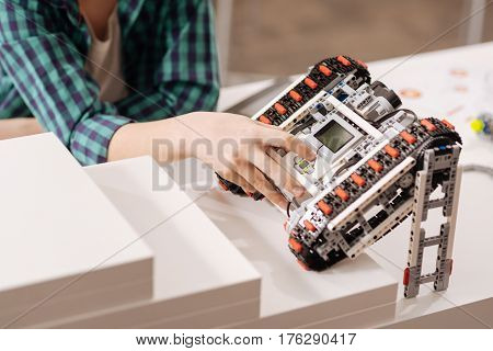 Modernized device. Skilled smart young boy sitting in the studio while expressing gladness and programming robot