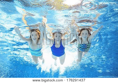 Family swimming in pool under water, happy active mother and children have fun, fitness and sport with kids on summer vacation