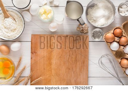 Baking background Top view with copy space. Cooking ingredients for dough and pastry making and wooden pizza board on white rustic wood. Mockup for menu, recipe or culinary classes.
