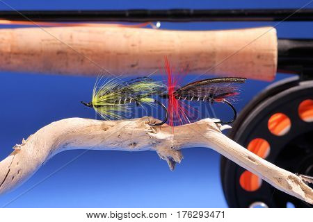 Two large hand tied salmon flies sitting on a piece of driftwood.