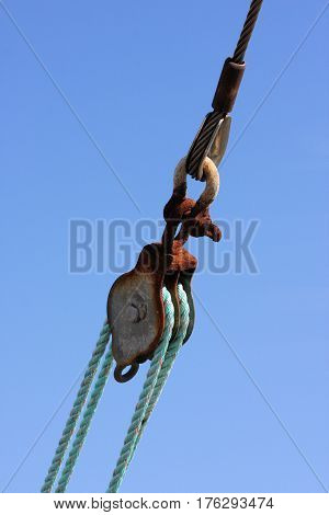 Rusty block pulley, rope, and steel cable of a large fishing trawler against a blue background.