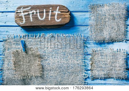 Burlap frames on blue painted wood boards. Dark wooden signboard with text 'Fruit' as title bar. Structured shabby style background for natural food and drink industry
