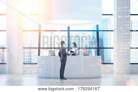 Side view of a businessman standing near a round reception desk and talking to the receptionist. Toned image. Double exposure