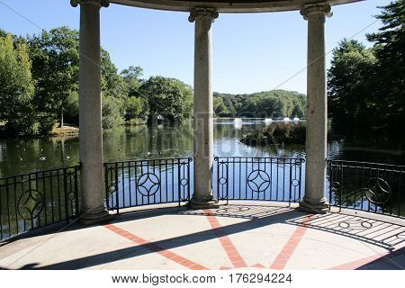 Three concrete pillars of a large gazebo on the shore of a small park lake.
