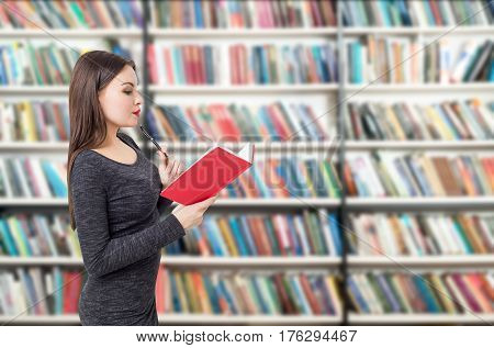 Side view of a woman reading a red book in a library. Concept of reading and working with information.