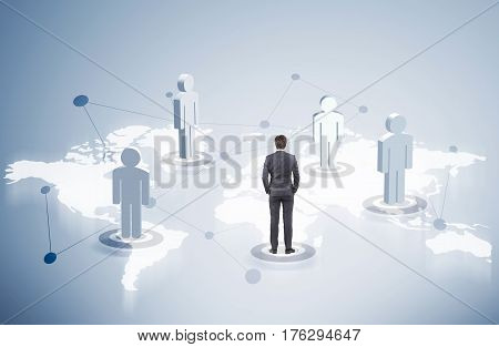 Rear view of a businessman standing among people figures on a world map.
