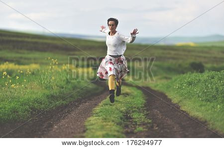 Freedom Concept. Cheerful Girl Running On A Countryside Road