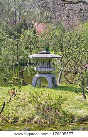 Traditional Japanese stone lantern in Japanese garden in springtime