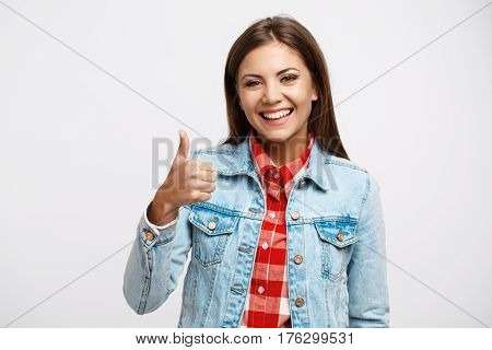 Closeup portrait of smiling young woman in cool spring look showing thumb up looking straight