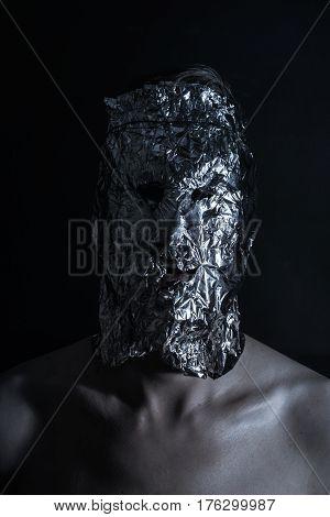 A dark portrait of man dressed in terrible metal mask