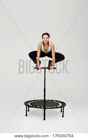 Young sporty woman jumping high on rebounder with bending knees holding handle looking straight