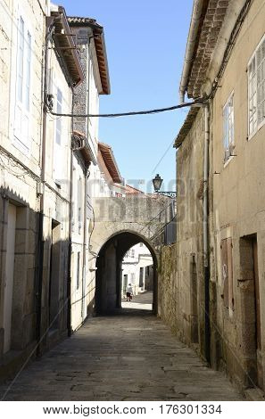 TUI, SPAIN - AUGUST 7, 2016: Woman in an alley with a Small arch of Tui a town of the province of Pontevedra in Galicia Spain.