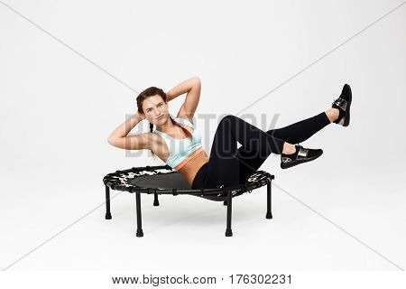 Cheerful sporty woman doing abdominal crunches sitting on rebounder looking happy isolated on white background