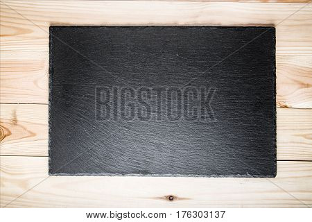 black slate board for serving on a light wood surface top view