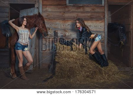 Two women are on the ranch near the stables they talk to each other.
