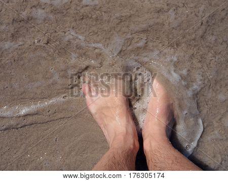 POV feet on a sandy beach on Phuket