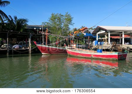 Few fishing boats on front of a village Thailand