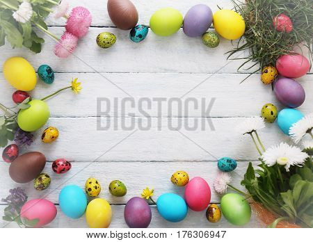 Multicolored eggs with flowers on white wood. Easter conceptual background. Top view