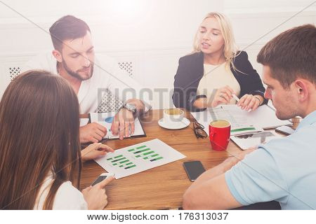 Business meeting, analyzing sales. Young hipsters businessmen and women at modern office, team discussion at workplace, look on diagram. Brainstorming and communication with partners for startup.