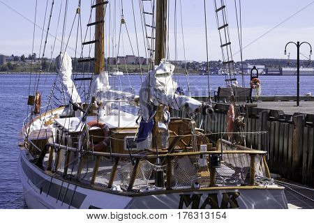 Halifax, Nova Scotia, September 23, 2015 -- Wide view of a wood trimmed sail boat docked at the Halifax Harbor on a beautiful bright sunny day in September with Dartmouth buildings in the background in Halifax, Nova Scotia