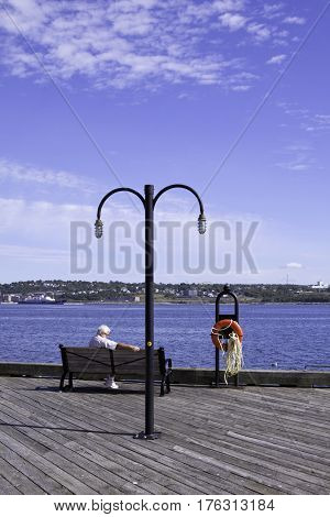 Halifax, Nova Scotia, September 23, 2015 -- A man relaxes on the park bench overlooking Halifax Harbor with a orange lifesaver on a stand to the right, on a beautiful bright sunny day in September in Halifax, Nova Scotia