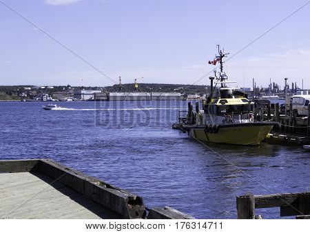 Halifax, Nova Scotia, September 23, 2015 -- Wide view of the Pilot a rescue boat in Halifax Harbor and a motor boat speeding by in the distance on a bright sunny day in September in Halifax, Nova Scotia.