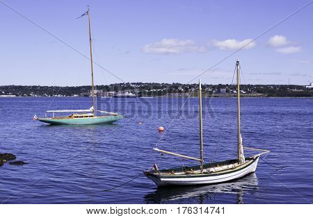 Halifax, Nova Scotia, September 23, 2015 -- Two small sailboats sit docked in the Halifax Harbor with Dartmouth on the background on a bright sunny day in September in Halifax, Nova Scotia