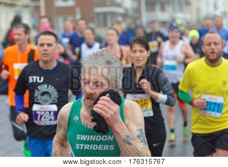 BRIGHTON GREAT BRITAIN - FEB 26 2017: Senior man with beard and competitors r running in the Vitality Brighton half marathon competition. February 26 2017 in Brighton Great Britain