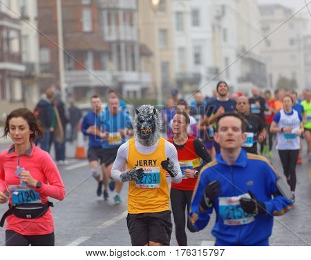 BRIGHTON GREAT BRITAIN - FEB 26 2017: Man dressed as a werewolf and competitors r running in the Vitality Brighton half marathon competition. February 26 2017 in Brighton Great Britain