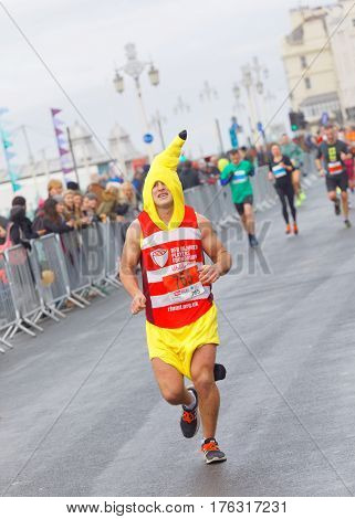 BRIGHTON GREAT BRITAIN - FEB 26 2017: Man dressed as a banana and competitors r running in the Vitality Brighton half marathon competition. February 26 2017 in Brighton Great Britain