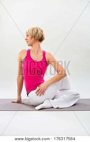 Woman exercising yoga indoor-Half lord of the fishes pose/Ardha Matsyendrasana