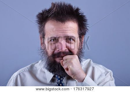 Strange looking guy with weird hair and beard worried about something he did - biting his fist