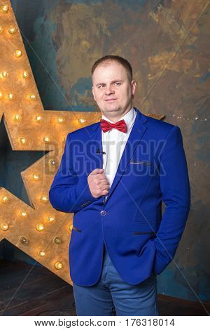 Happy elegant man in blue suit is standing with crossed hands at wall background