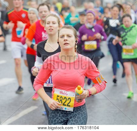 BRIGHTON GREAT BRITAIN - FEB 26 2017: Beautiful girl and competitors running in the Vitality Brighton half marathon competition. February 26 2017 in Brighton Great Britain