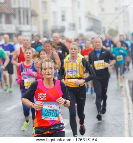 BRIGHTON GREAT BRITAIN - FEB 26 2017: Young woman and competitors running in the Vitality Brighton half marathon competition. February 26 2017 in Brighton Great Britain