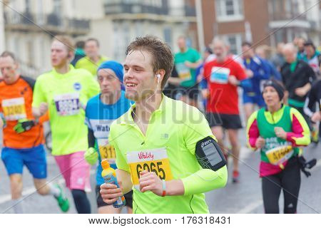 BRIGHTON GREAT BRITAIN - FEB 26 2017: Young smiling man and competitors running in the Vitality Brighton half marathon competition. February 26 2017 in Brighton Great Britain